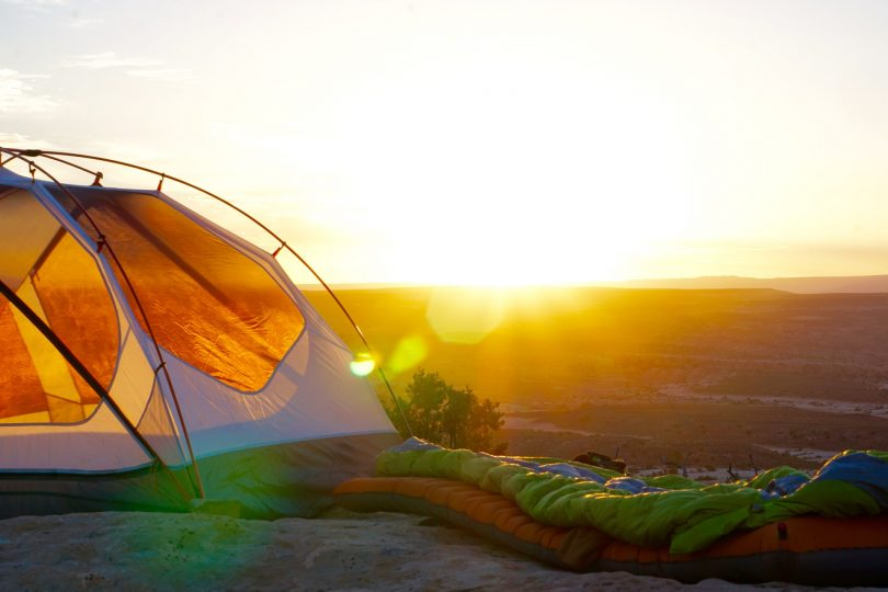 A green sleeping bag outside a camping tent in the sunset