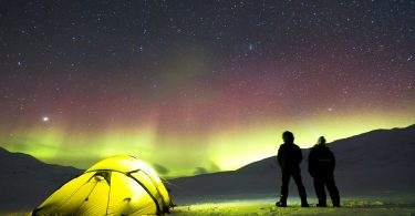 a neon tent underneath the northern lights