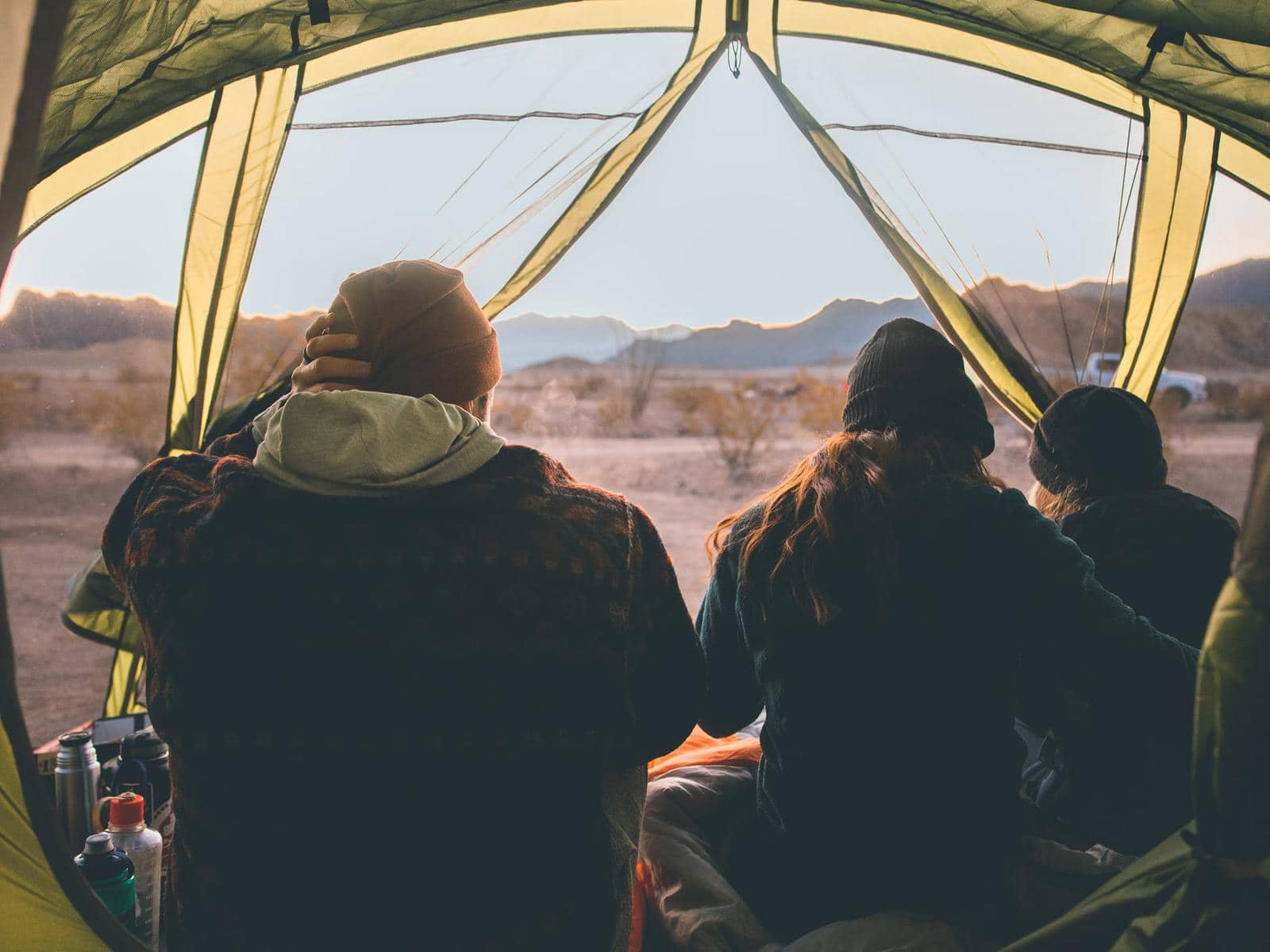 a family of three looking out from a yellow see through tent