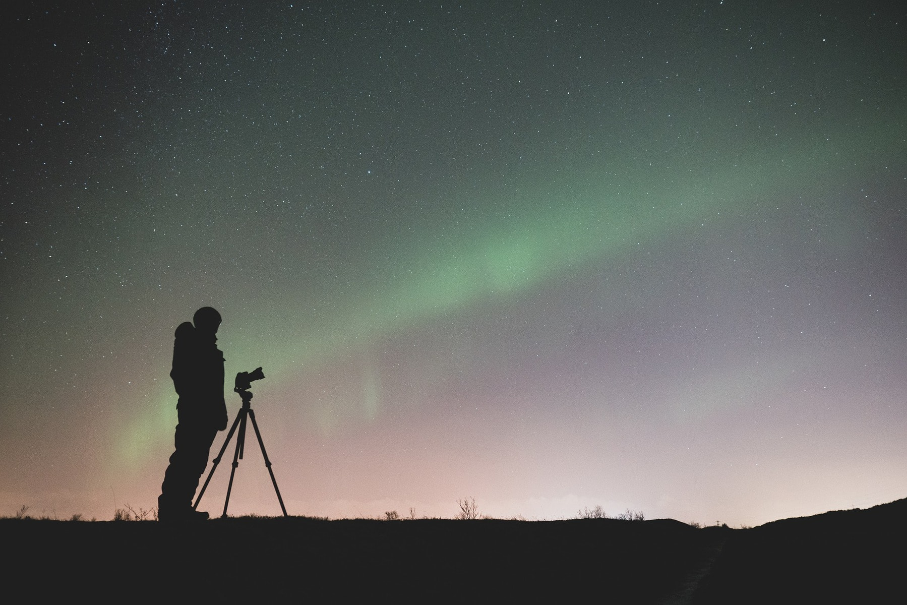 Man with tripod at dusk