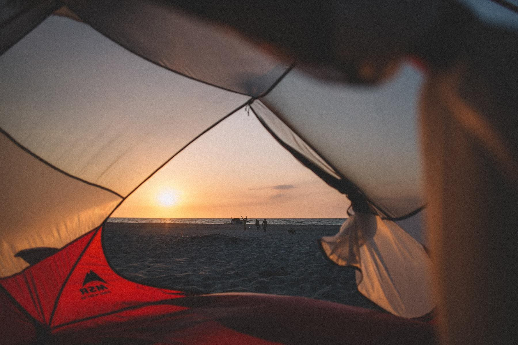 a tent on the beach at sunset