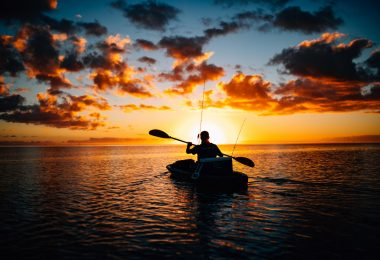 A silhouette of a person in a kayak on the sea during sunset