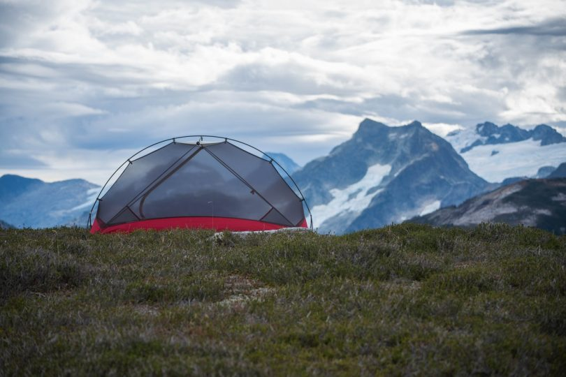 a screen tent on some grass in front of a mountain