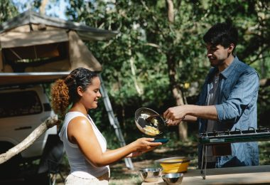 a man putting eggs on a woman's plate outdoors